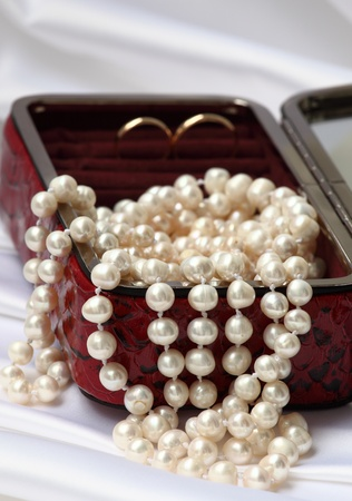 Pearls and gold rings in red jewelry box on neutral background photo