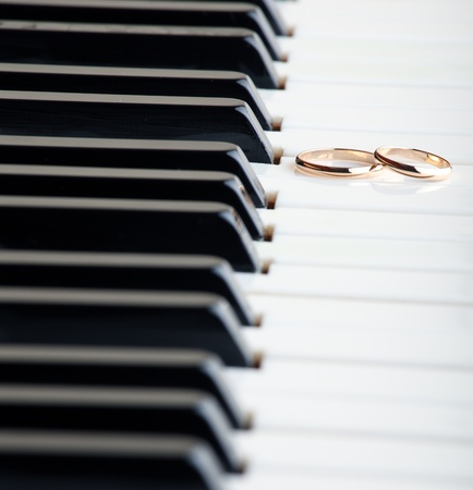 Gold wedding rings on a piano photo