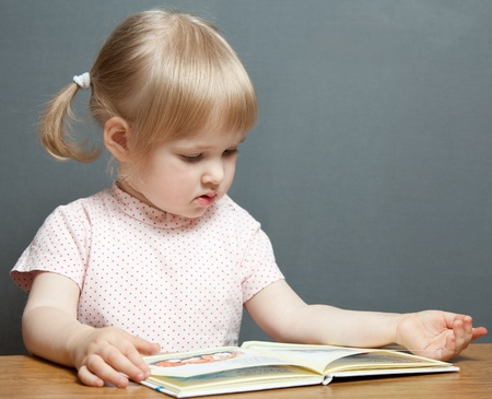 intresting: The baby girl is reading the book Stock Photo