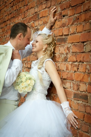 hugging legs: Bride and groom near the wall of brick