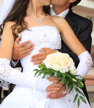 bridal bouquet: Embracing bride and groom. Wedding day