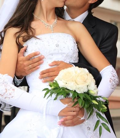 bruidsboeket: Het omarmen van bruid en bruidegom. Trouwdag