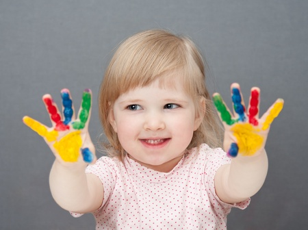 Baby is drawing paint. Grey background Stock Photo - 10966785