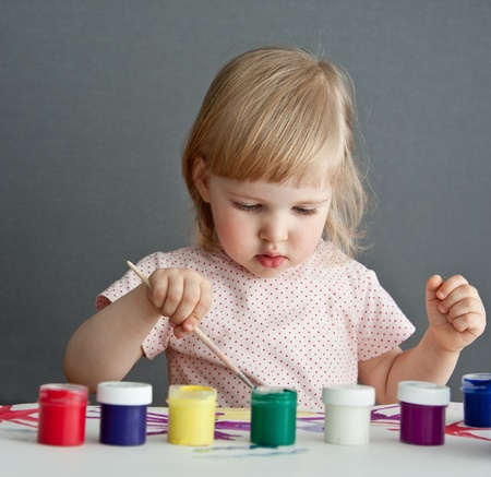 Baby girl is drawing of paint. Grey background Stock Photo - 10966789