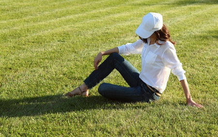 Girl sitting on the grass photo