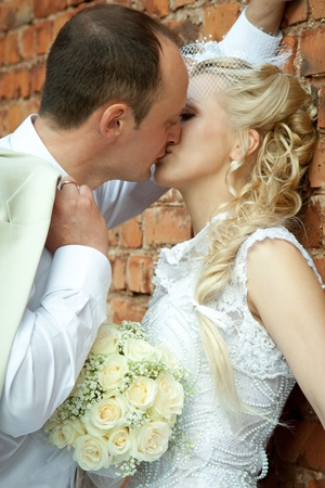 Kissing bride and groom near the wall photo