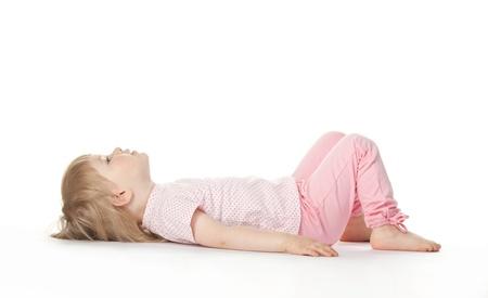 The baby girl is lying on the floor bend one