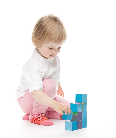 baby blocks: The baby girl plays with bricks on white background