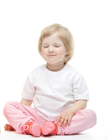 The baby girl is sitting on the floor to fold legs and close eyes Stock Photo