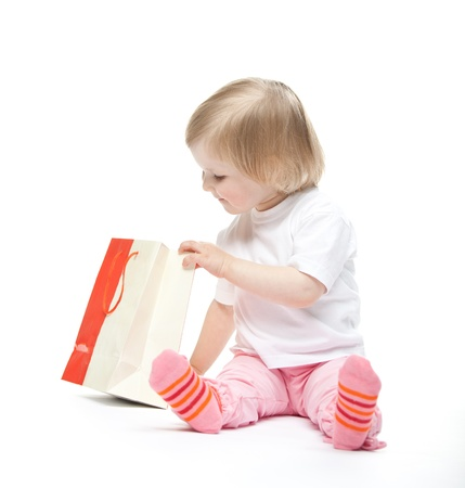 The baby girl finds a present. White background photo