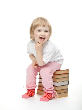 The baby girl is sitting on the pile of books and proping up chin