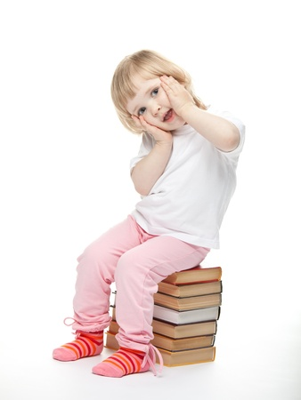 The baby girl is sitting on the books. White background photo