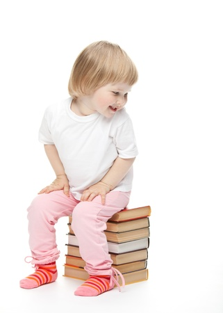 The baby girl is sitting on the books and turning back. White background photo