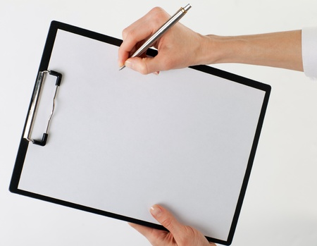 Human hands holding blank sheet of paper in a clipboard and a pen; isolated on neutral background photo