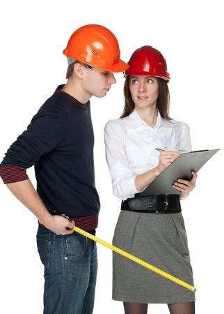 Young man with a tape measure and young woman in hard hats discussing details of  construction process; isolated on white Stock Photo - 11173685