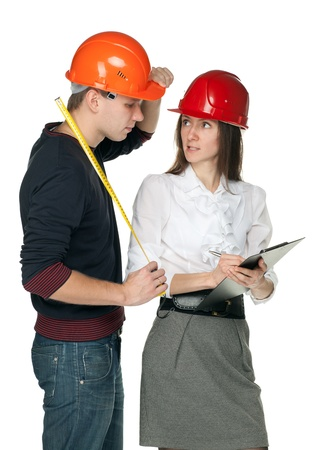 Young man with a tape measure and young woman in hard hats discussing details of  construction process; isolated on white Stock Photo - 11173688
