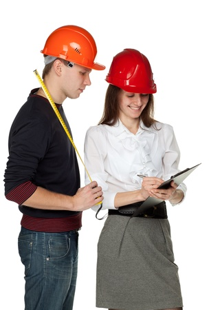 Young man with a tape measure and young woman in hard hats discussing details of  construction process; isolated on white Stock Photo - 11173675
