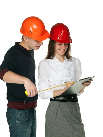 Smiling young man with a tape measure and young woman in hard hats discussing details of  construction process; isolated on white Stock Photo - 11173681