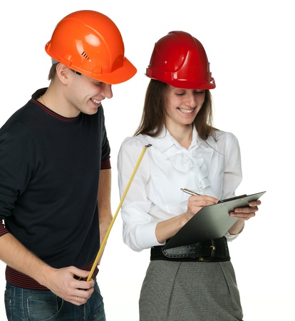 Smiling young man with a tape measure and young woman in hard hats; isolated on white Stock Photo - 11174341