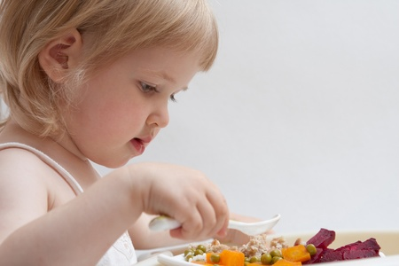 Cute baby girl holding a spoon and eating vegetables and porridge