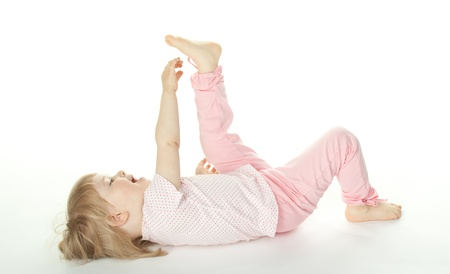 The baby girl is lying on the floor. White background