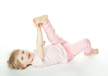 The baby girl is lying on the floor and raising ones hand and leg