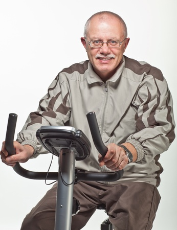 sport clothes: Man in sport clothes exercising on a bicycle trainer on neutral background Stock Photo