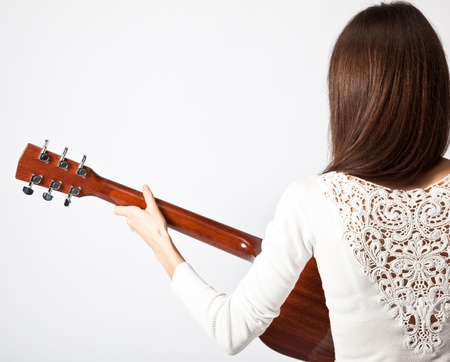 Young brunette playing guitar; isolated on neutral background photo
