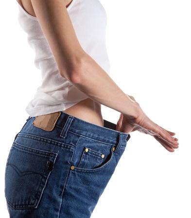 body shape: Slim giovane donna in jeans grande mostrando quanto ha perso peso, isolato su bianco