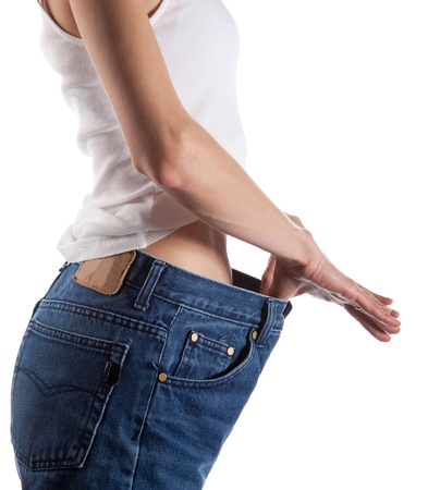 Slim young woman in big jeans showing how much she lost weight; isolated on white Stock Photo