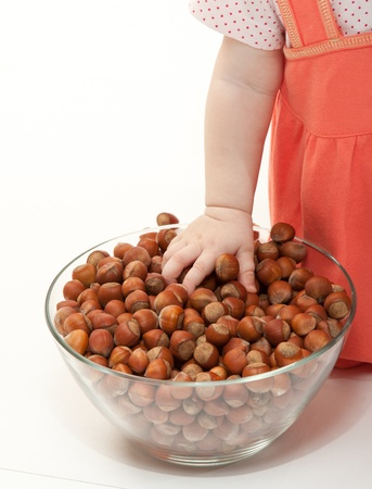 The baby girl is playing with hazelnuts on white background Stock Photo - 11283301