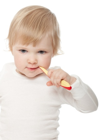 The active baby girl with a tooth-brush on white background photo
