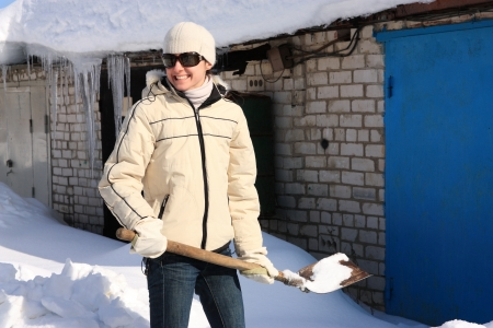 Cheerful young woman removing snow with a shovel; manual snow removal photo