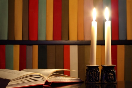 Opened book, candles and bookshelves in the background illustrating concept that knowledge is light and ignorance is darkness photo
