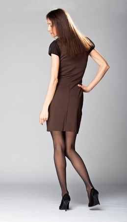 Full length portrait of an attractive young brunette in brown dress on neutral background photo