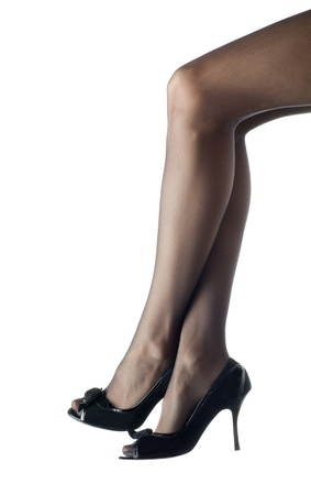 Young woman's long legs in high-heeled black shoes; isolated over white background photo