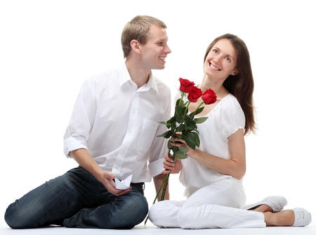 Happy smiling young guy and girl with red roses sitting together on the floor; isolated on white background photo