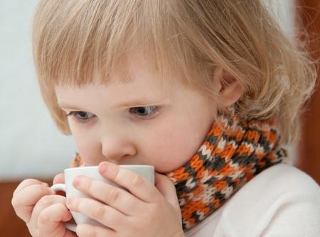 enfant malade: La petite fille avec une tasse de th�. La fille se redresse. Banque d'images
