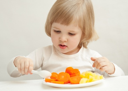The baby girl is eating vegetables Stock Photo