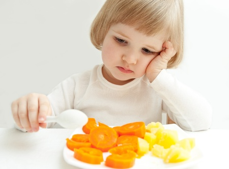The girl does not eat the vegetables. photo