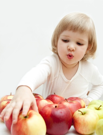 The baby girl is selecting a tasty apple