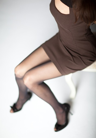 Above view of sexy young woman wearing dress and high-heeled shoes sitting on a chair  Stock Photo - 11771626