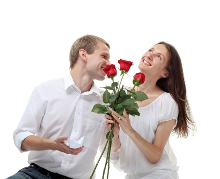 Smiling guy proposing engagement ring to his happy girlfriend, isolated over white background