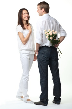 Romantic date: guy presenting flowers to young lady; isolated on white photo
