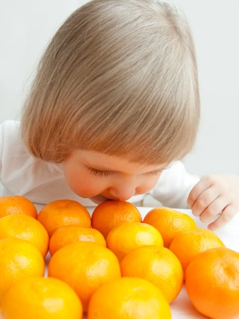 child food: The happy baby girl is smelling tangerines.