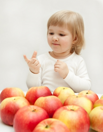 The baby girl is counting apples on one photo