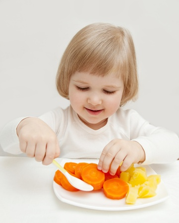 The smiling baby girl eating vegetables.