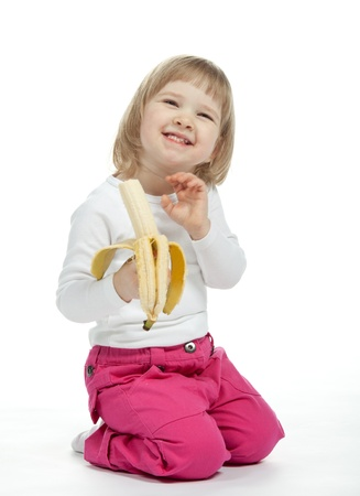 The smiling baby girl is eating ripe banana; white background photo