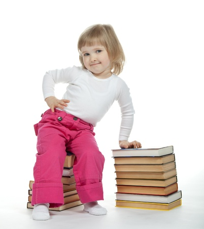 The little girl sitting on the stack of books; white background Stock fotó