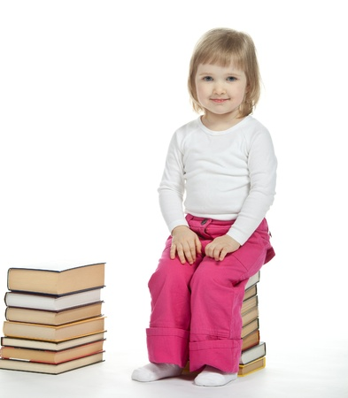 The little girl sitting on the stack of books; white background